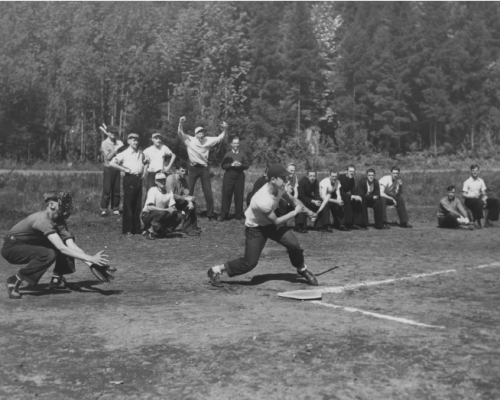A Group Of People Playing Baseball On A Field